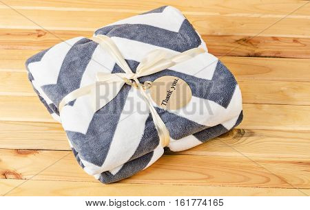 Blanket with ribbon and Thank you tag gift on wooden background.