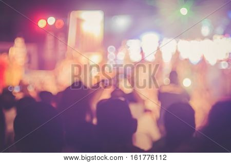 Blur People Taking Smart Phone In Night Outdoor Concert With Colorful Bokeh Abstract Background.