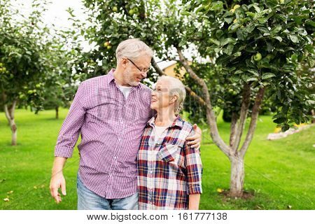 farming, gardening, old age and people concept - happy senior couple hugging at summer garden