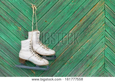The old skates hanging on a wooden wall. Texture background