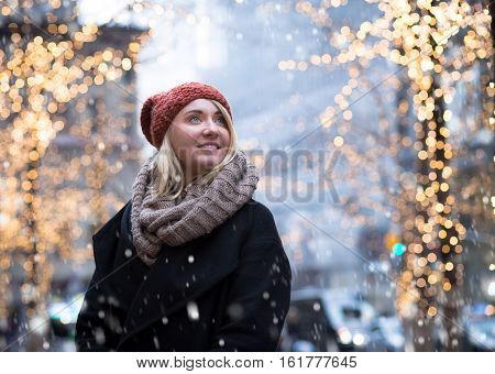 Portrait of young attractive woman with holiday lights in snowy day photographed in NYC in December