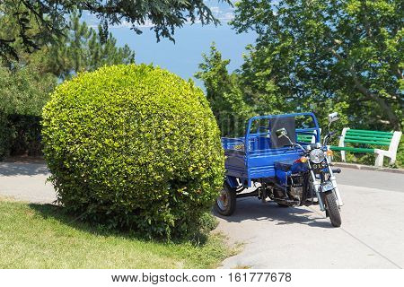 Motorcycle in the botanical garden. Exterior landscape complex on the beach