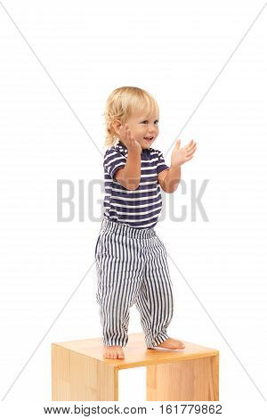 Cheerful boy standing on little table and clapping with hands and dancing