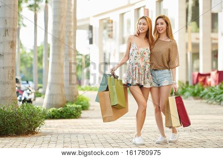 Attrative smiling girls with many shopping bags standing outdoors