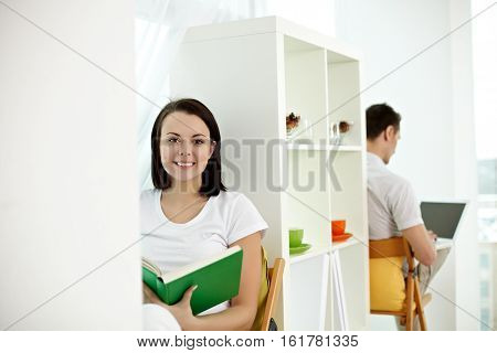 Young girl reading sitting with a book and a man working with computer