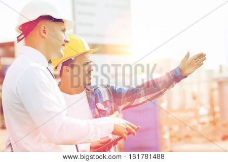 business, building, teamwork, technology and people concept - builder and architect or businessman in hardhats with tablet pc computer outdoors