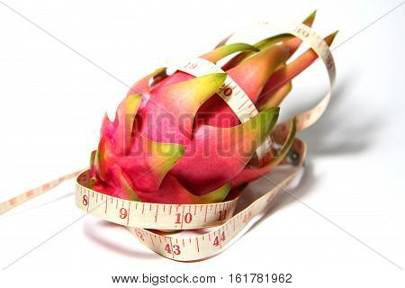 Pitaya with a tape measure on white background