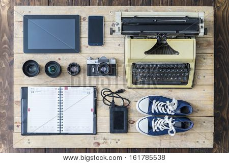 Outfit of a stylish traveler or a freelance journalist. Set of different objects and equipment: tablet, phone, organaizer, glasses, camera, lenses, hard drive, gumshoes, and typing machine.