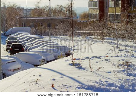 Cars covered with fluffy snow on the parking lot in a residential area at a sunny morning