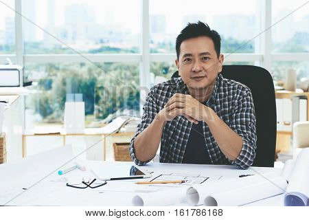 Portrait of smiling Singaporean engineer at his workplace