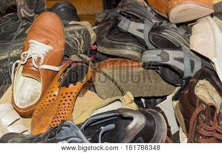 Piled up a bunch of old different worn mens and womens footwear for different seasons