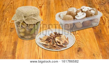 Dried boletus pickled button mushrooms in glass jar fresh uncooked button mushrooms in a transparent plastic tray on a surface of old wooden planks