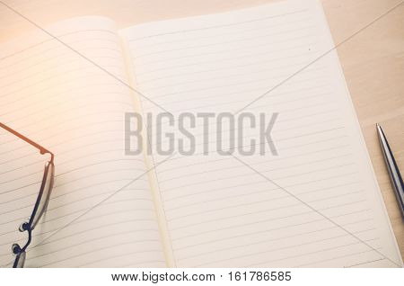 Copy Space Of Note Book With Pen And Glasses On Wood Table Background.
