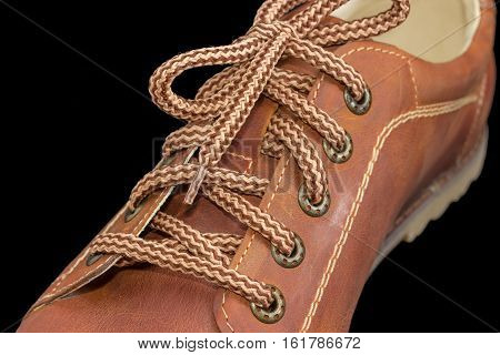 Fragment of new leather brown mens shoe with a shoelaces and eyelets on a dark background closeup