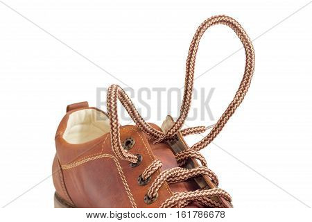 Synthetic shoelaces on brown mens shoe with an eyelets closeup during lacing on a light background