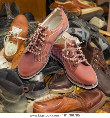 Pair of new leather brown mens shoes with a shoelaces on a pile of old different worn footwear