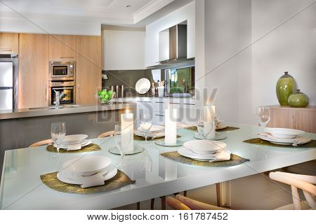 Shiny dining table ready to serve with dishes wine glasses and flashing white candles. A leaf shaped braid is below the plates. The kitchen has wall oven stove fixed next to the refrigerator a faucet on the counter top table with fruits.