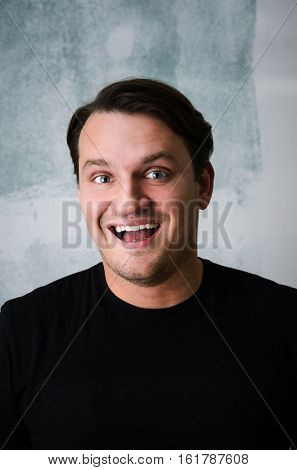 Portrait of young adult happy man against grunge wall