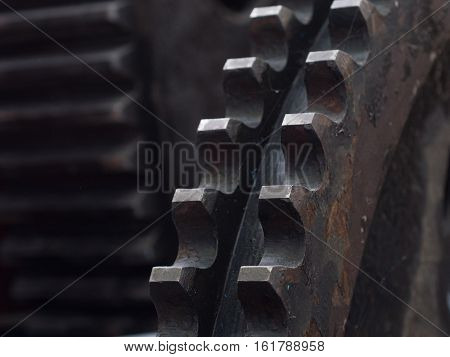 Detail of old rusty cogwheel in industrial environment. Very shallow depth of field with only the nearest teeth in focus.