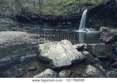 Beautiful Cross Processed Waterfall Landscape Image In Forest During Autumn Fall In Wales Uk