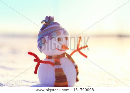 White Christmas snowman on snow. Winter sun shine on snowman. Snowman with hat in sunny christmas morning. Colorful winter background.