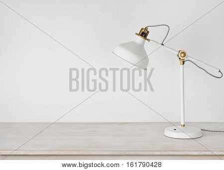 White lamp on wooden desk in room with copy space
