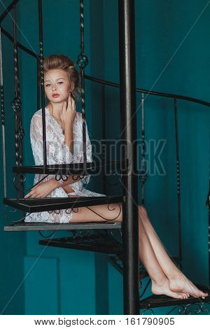 Beautiful blond bride in white negligee sitting on the black wrought iron stairs