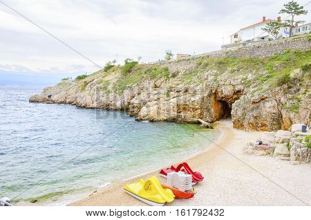 Zgribnica beach in Vrbnik town Krk island Croatia. A blue flag crystal clear sea with paddle pedal boats restaurant pebble and concrete shore in the medieval picturesque village with narrow streets on the east.