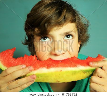preteen handsome boy eat water melon on blue wall background close up portrait