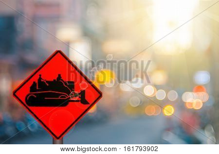 Construction Tractor Warning Sign On Blur Traffic Road With Colorful Bokeh Light Abstract Background