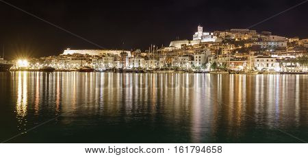 Skyline of Ibiza Dalt Vila downtown at night with light reflections in the water and sailing boats