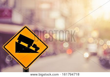 Down Hill Warning Sign On Blur Traffic Road With Colorful Bokeh Light Abstract Background.