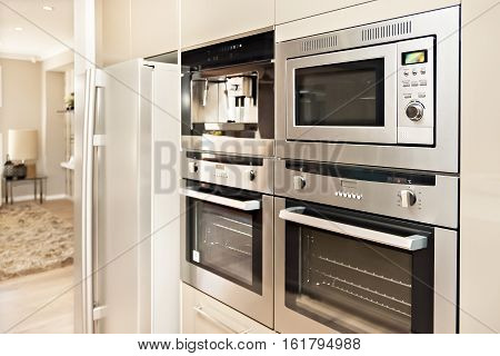 Luxurious kitchenware including silver oven and refrigerator in the kitchen which has a wooden floor Pantry cupboards are light brown color and installed around the cooker and fridge.