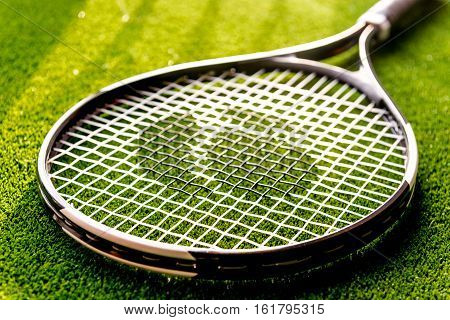 tennis racket on green background close up.