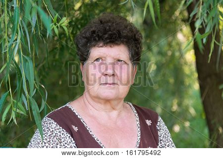 Mature woman with curly hair near a weeping willow