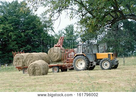 Farmer driving tractor and picking up haystacks in Savoy fields France