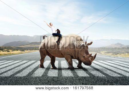 Businesswoman riding rhino . Mixed media