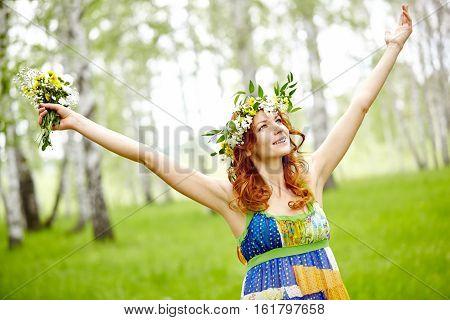 Beautiful woman wearing flower crown enjoying summer nature