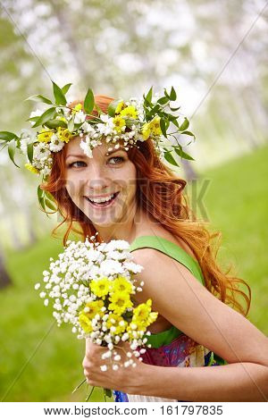 Outdoor portrait of laughing woman wearing flower crown holding wildflowers