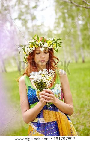 Thoughtful woman in sundress holding bunch of wildflowers