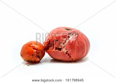 Two red rotten tomatoes isolated on white