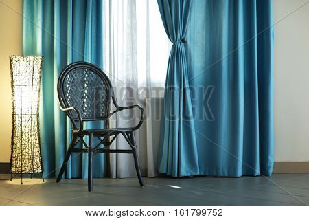 Chair, lamp and room window with white and blue curtains