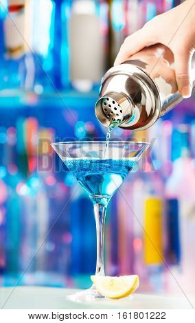 Hand of barman pouring liqueur from shaker to cocktail glass