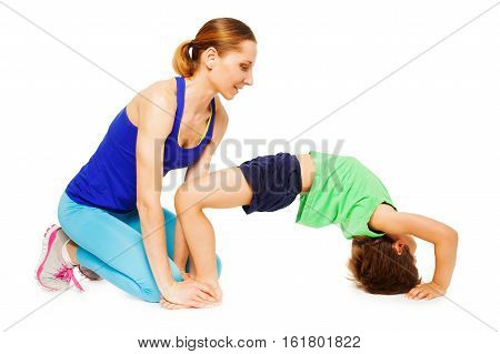 Female trainer teaching kid boy making a crab pose, isolated on white