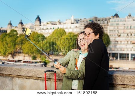 Two cute friends taking photo using a selfie stick at the embankment of the Seine River