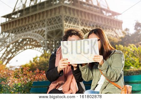 Two women sitting on a bench and looking at a paper map during their excursion in Paris