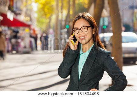 Happy Asian woman calling on the mobile phone on the street of Paris