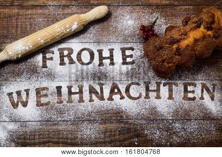 high-angle shot of a wooden table sprinkled with icing sugar or flour where you can read the text frohe weihnachten, merry christmas in german, a rolling pin and a christmas cake