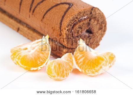Tasty cake roll and clementine isolated on white background
