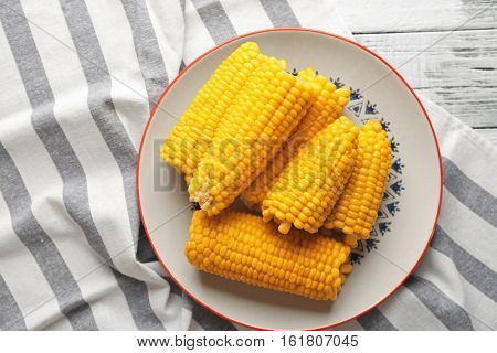 Plate with tasty boiled corncobs on kitchen table, top view